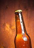 Tilted bottle of fresh beer with drops Royalty Free Stock Photos