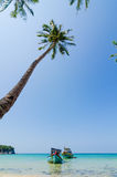 Tilted coconut trees by the beach with the boat and blue sky Royalty Free Stock Photo