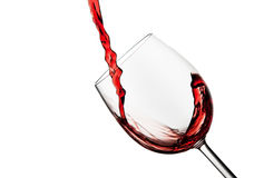 Tilted crystal wine glass with red wine. Against a white background Royalty Free Stock Images