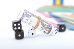 Tilted Dollar Bill With Black and White Dice Stock Photos