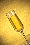 Tilted flute of golden champagne Stock Photo