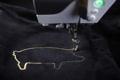 Embroidery machine stitching pig motive with gold yarn on black velvetely fabric. Tilted front view on embroidery machine stitching pig motive with gold yarn on stock photos