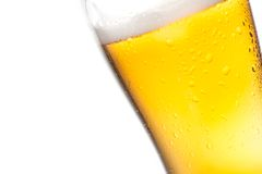Tilted glass of beer and drops on white background Stock Images
