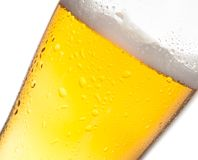 Tilted glass of fresh beer and drops on white Royalty Free Stock Photos