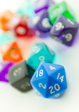 Tilted macro of blue twenty sided dice with other dice Royalty Free Stock Photos