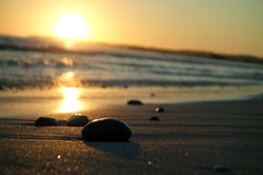Tilted Sunset. Rocks kiss the day goodnight as the sun sets over the tilted horizon Royalty Free Stock Photography