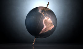 Tilted World Globe. A vintage world globe tilted and standing on a central axis on an isolated spotlit dark background Royalty Free Stock Photo