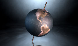 Tilted World Globe. A vintage world globe tilted and standing on a central axis on an isolated spotlit dark background Stock Image