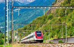 Tilting high-speed train on the Gotthard railway Stock Photo