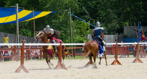 Tilting Knights 3. Two armored knights ride at one another in a jousting match during a Renaissance festival Stock Photography