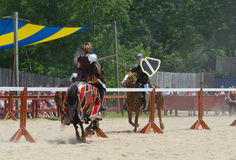 Tilting Knights 4. Two armored knights ride at one another in a jousting match during a Renaissance festival Royalty Free Stock Photography