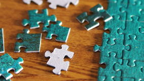 Tilting from puzzle pieces to complete puzzle stock footage