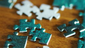 Tilting from unfocused puzzle pieces to focused and to unfocused again stock footage