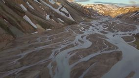 Tilt up from river delta to Icelandic snowy mountains. Tilting up from river delta to rainbow volcanic mountains in Iceland in Landmannalaugar at sunset. Aerial stock footage