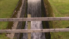Tilting up shot of a water canal. Tilting up shot of an old man made water canal. The old moss covered walls are surrounded by green fields stock video