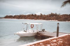 Tiltshift view of a white moored motorboat with marquee. True tilt-shift shot of a small white speedboat with a awning moored to a wooden pier with a lantern stock photos
