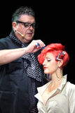 Tim Hartley makes hairdo for red hair model Stock Images