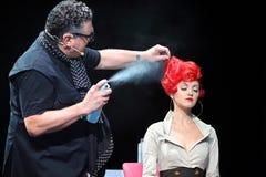 Tim Hartley pulvérise la laque sur le cheveu rouge du modèle Image stock
