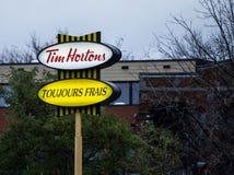 Tim Hortons logo przed jeden ich restauracje w Quebec z ich sogan w Francuskim Tim Hortons jest kawiarni & fastfood gatunkiem zdjęcie stock