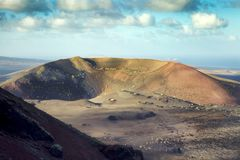 A dormant Caldera is lit by the sun in the National Park of Timanfaya in Lanzarote. Timanfaya, Lanzarote / Spain - 04/03/2016: Clouds form over a dormant Stock Photo