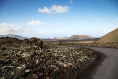 A Road leads through the volcanic lava fields of Timanfaya National Park in Lanzarote. Timanfaya, Lanzarote / Spain - 04/03/2016: A deserted road leads through Stock Image