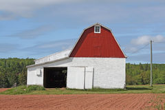 Timber barn. Red and white gambrel roofed timber barn on a farm Stock Photos
