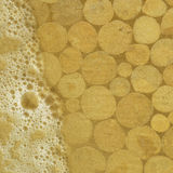 Timber beneath the sands and surf bubbles. Stock Image
