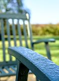 Close-up of new outdoor, timber garden furniture seen after a heavy downpour. The timber built seating is seen in an outdoor location during the summer after a Royalty Free Stock Photography