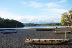 Timber canoe at sand near river Stock Image