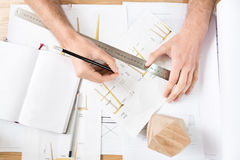 Timber craftsman drawing drafts at workplace Royalty Free Stock Images