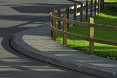 Timber fence and road. Turn of road with fence Stock Photos