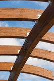 Timber frame arch against blue sky midday underneath view. Timber frame arch against blue sky and white clouds midday underneath view royalty free stock photography