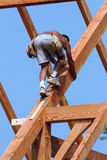Timber frame construction worker. A barn builder scales a large rafter stock photo