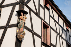 Timber framing house with religious statue Stock Photos