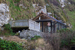 A timber glass summerhouse with decking in a very unusual location at the bottom of a cliff at the harbor in Ballintoy on the Nor Royalty Free Stock Photo