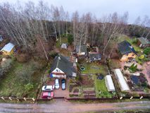 Timber house with courtyard, barns and small garden is on lake shore. Aerial view at spring season. Russia Royalty Free Stock Photo