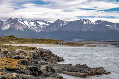 Timber house in Island and mountains view in Beagle Channel - Ushuaia, Tierra del Fuego, Argentina Royalty Free Stock Images