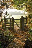 Timber kissing gate autumn. Timber kissing gate on edge of woodland footpath giving public access across farmland with autumn colours on misty morning Essex Royalty Free Stock Image