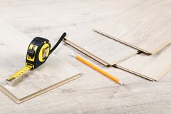 Laminate flooring with pencil. Timber laminate flooring with pencil and measuring tape stock photography
