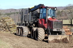 Timber Logging Truck Transport. An empty timber truck or tractor tailer with hydraulic arm and claw and plough  stands alongside large stockpiles of newly felled Royalty Free Stock Photo