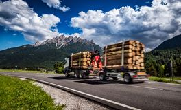 Timber truck rushes down the highway in the background the Alps. Royalty Free Stock Image
