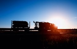 Timber truck transports timber logs and timber against the backdrop of a sunset and a blue sky, logistics and freight concept, royalty free stock images