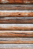 Timber wall of old loghouse. Wood wall is made of logs. This is the timber background of old rough logs weathered with deep cracks Stock Photography