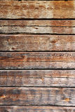 Timber wall of old wooden house. Wood wall is made of boards. This is the timber background of weathered planks with deep cracks Stock Images