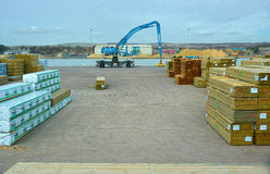 Timber yard dockside with grabber Royalty Free Stock Image