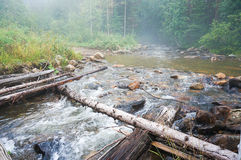 A timbered bridge across. A timbered handmade bridge across the mountain creek in woods Royalty Free Stock Photos