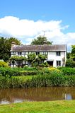 Timbered cottage and river, Eardisland. Royalty Free Stock Photography