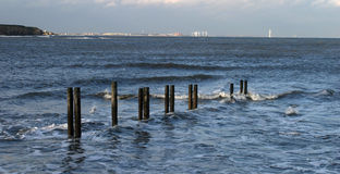 Timbers and tide. Timbers in water with Blythe in background Royalty Free Stock Image