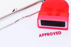 Timbre approuvé rouge sur le livre blanc avec la poinçonneuse et le presse-papiers en caoutchouc Photos libres de droits