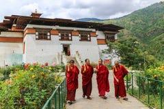 Timbu, Bhután - 15 de septiembre de 2016: Cuatro monjes que caminan en el jardín de Simtokha Dzong, Timbu, Bhután Foto de archivo libre de regalías
